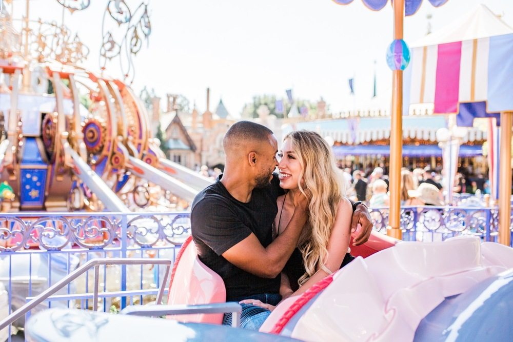An engaged couple sit in the Dumbo ride at Disneyland