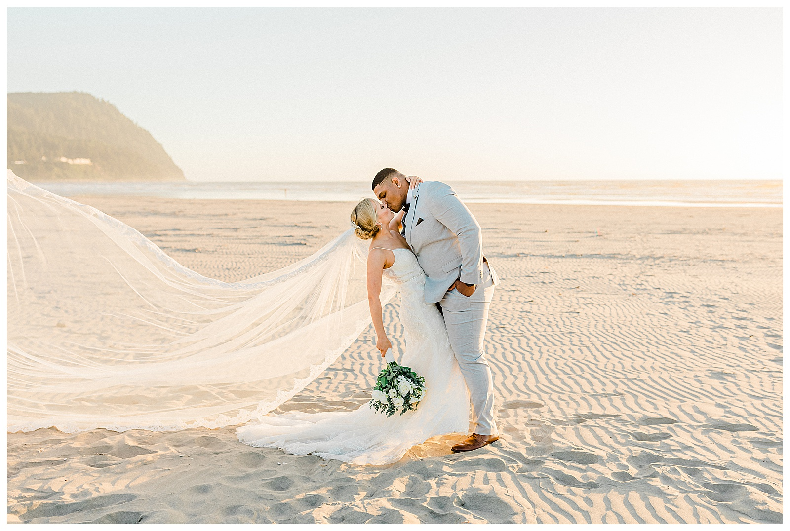 A bride and groom kiss at sunset on the beach as her veil flows behind her