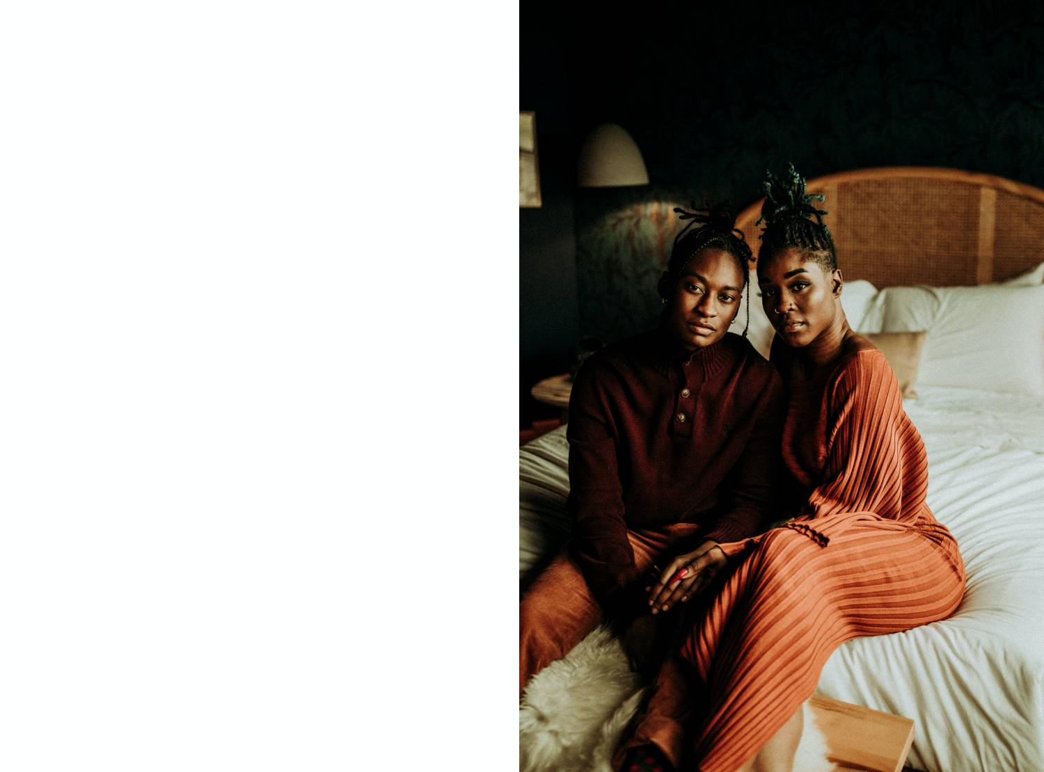 Photo: Fernweh & Fair's portrait of two Black people sitting close together on a cozy bed, gazing solemnly into the camera.