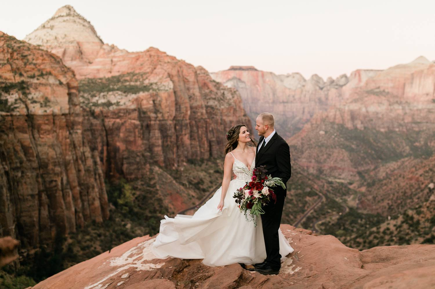 A bride and groom gaze into one another's eyes as they stand at the edge of a red rock cliff overlooking a tremendous canyon