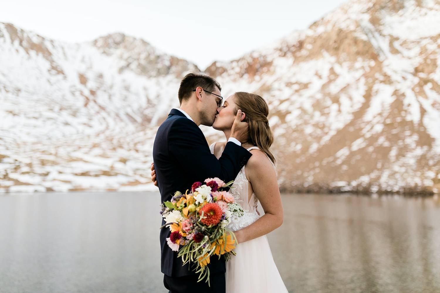 A bride a groom kiss lightly beside a shimmering lake in the shadow of a huge, snow-covered mountain