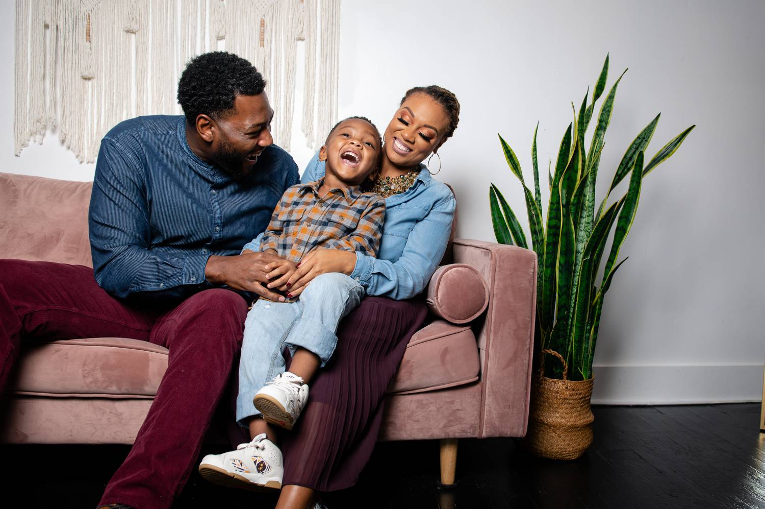 A Black family snuggle close together on a rose-colored couch in their living room