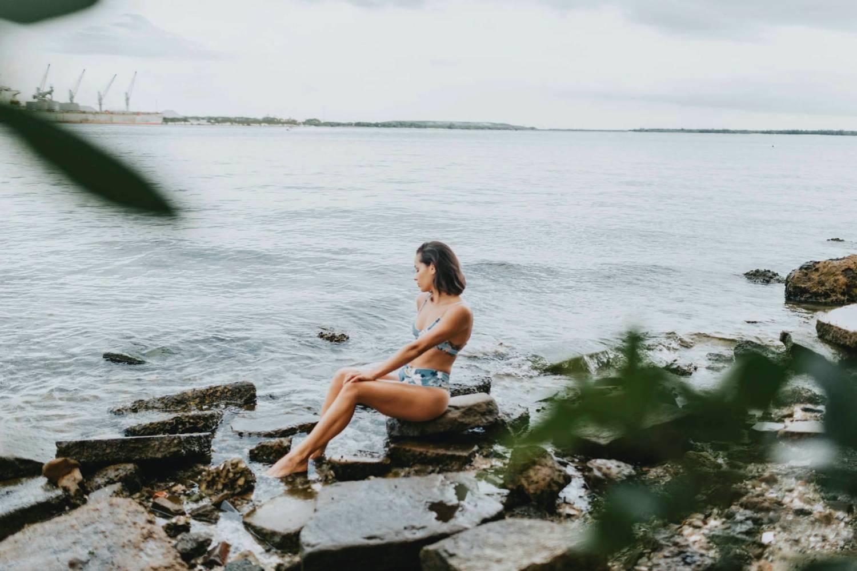 Photo: Grace Jicha's portrait of a woman in a blue bikini sitting on a rock at the edge of a lake.