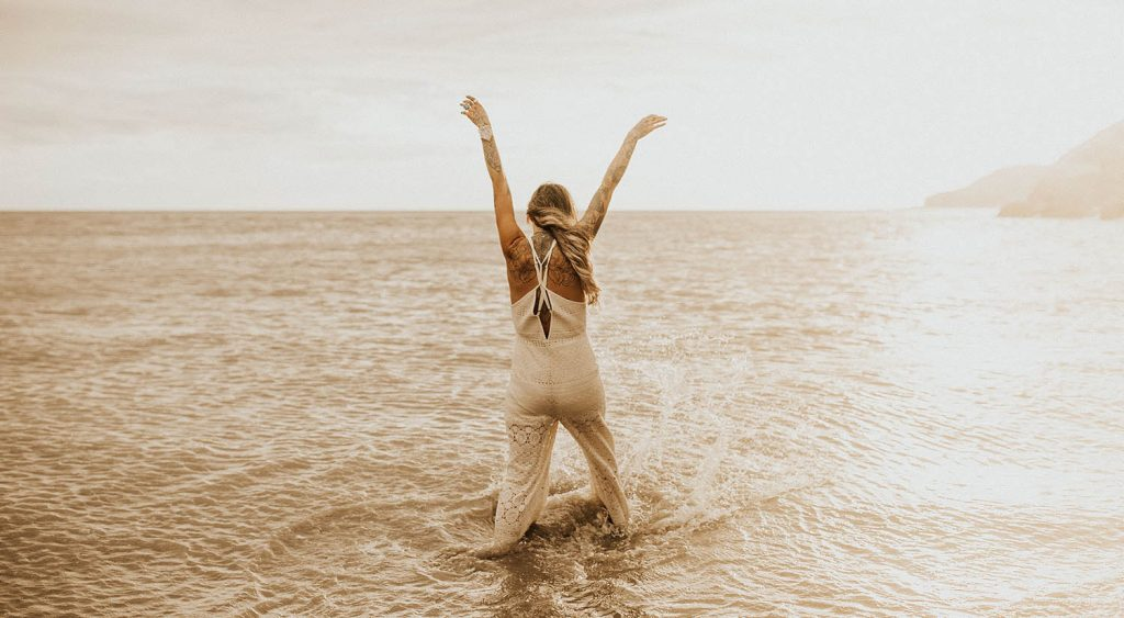 A woman in a white lace jumpsuit stands in the ocean and throws her hands up toward the sky as the sun sets