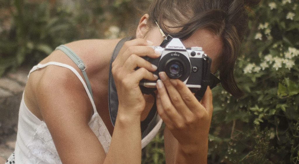 A woman leans forward as she composes a photograph with the camera held up to her face.