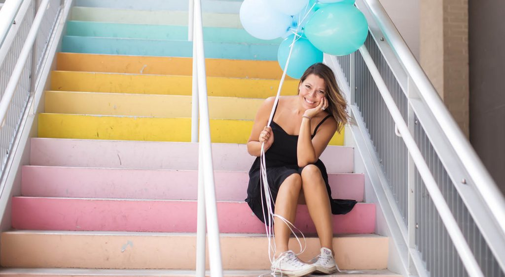 Headshot of photographer Shalonda Chaddock wearing a black sundress and white sneakers against a pastel rainbow background for episode 41 of Find Your Focus with ShootProof