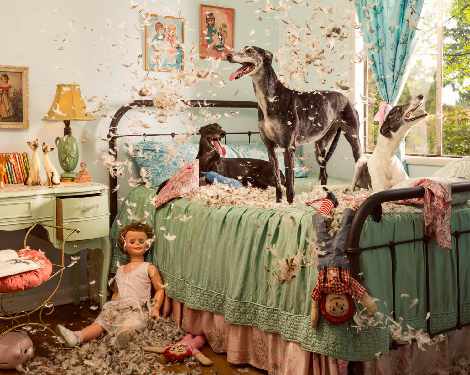 Photo: Holly Andres's photograph of greyhounds playing with feather pillows in a colorfully decorated room fills with trinkets, figurines, and dolls.
