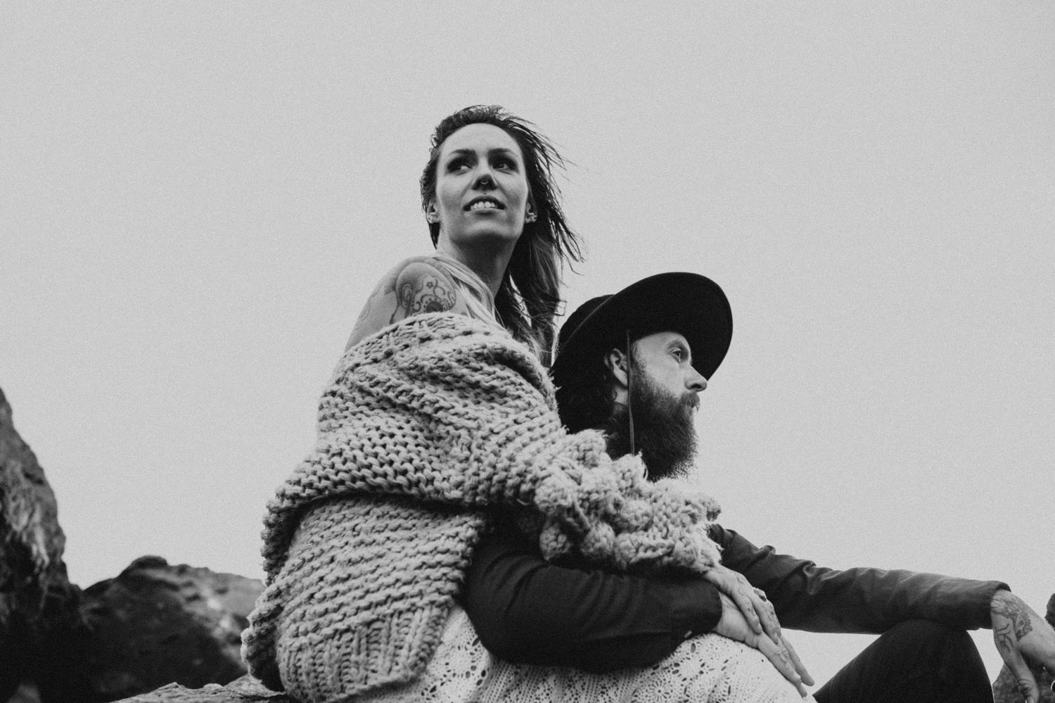 A woman in an oversized sweater sits behind a man with a beard as they sit outside against a gray sky.