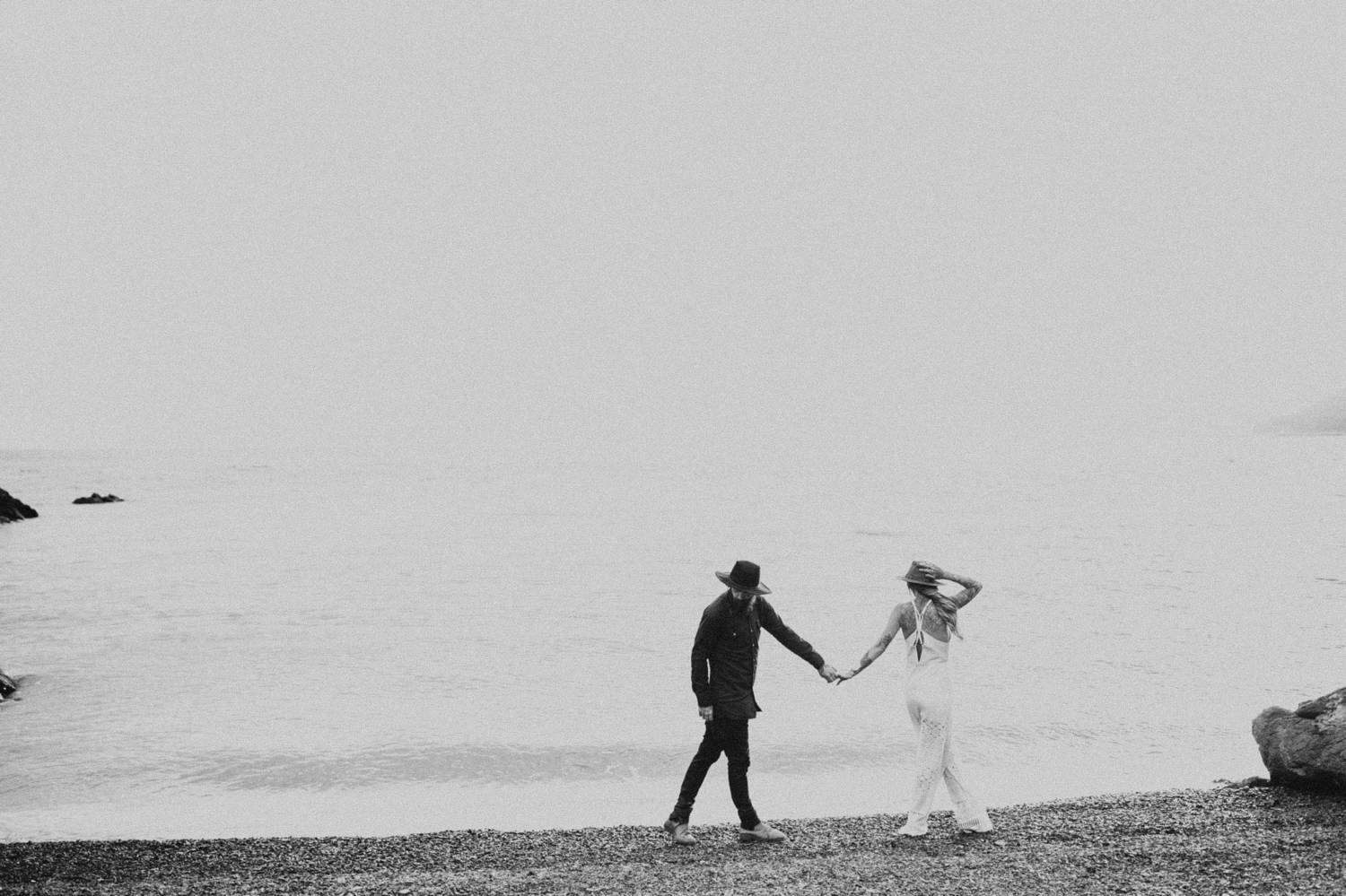A man dressed in black holds hands with a woman dressed in white as they stroll along the beach in this moody black and white photo by Brittany Boote