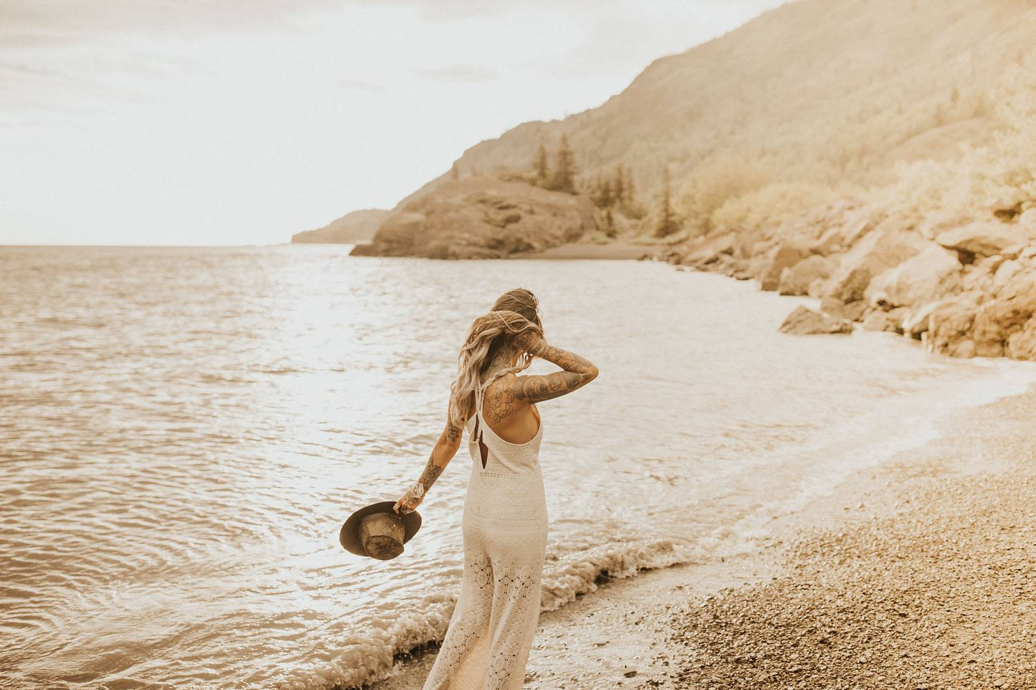 A woman in a white lace jumpsuit carries a felt had in one hand while holding her hair back with the other. She is strolling along the shore of a mountain lake.