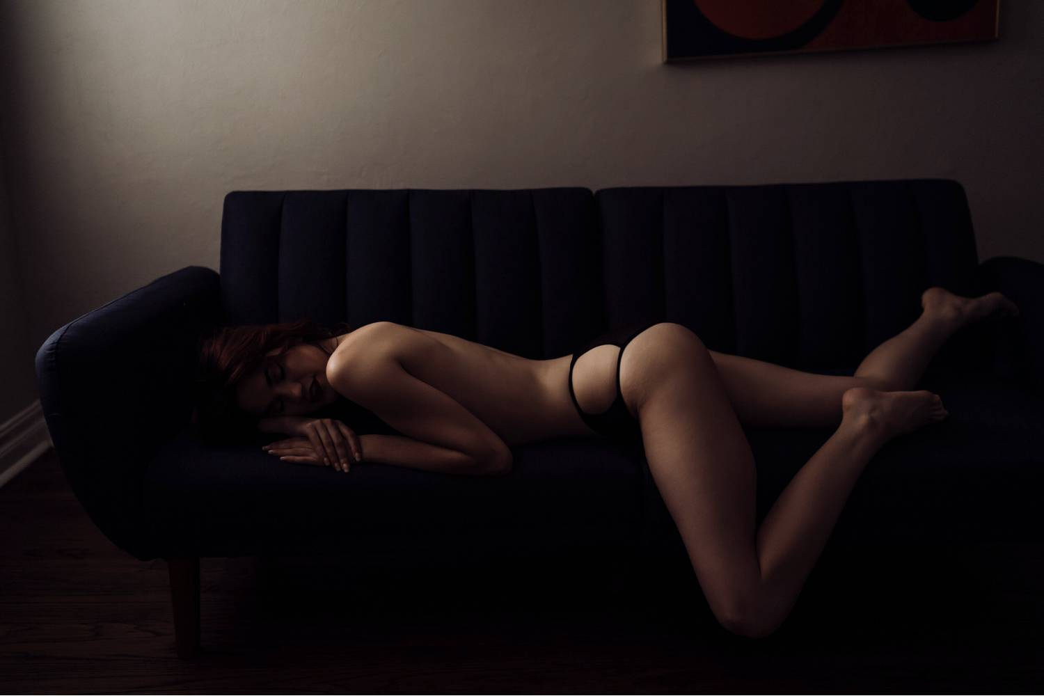 Photo: Intimate Lens Studio's portrait of a woman lying nearly naked on a sofa. The natural light spills across her back and hip as she reclines.