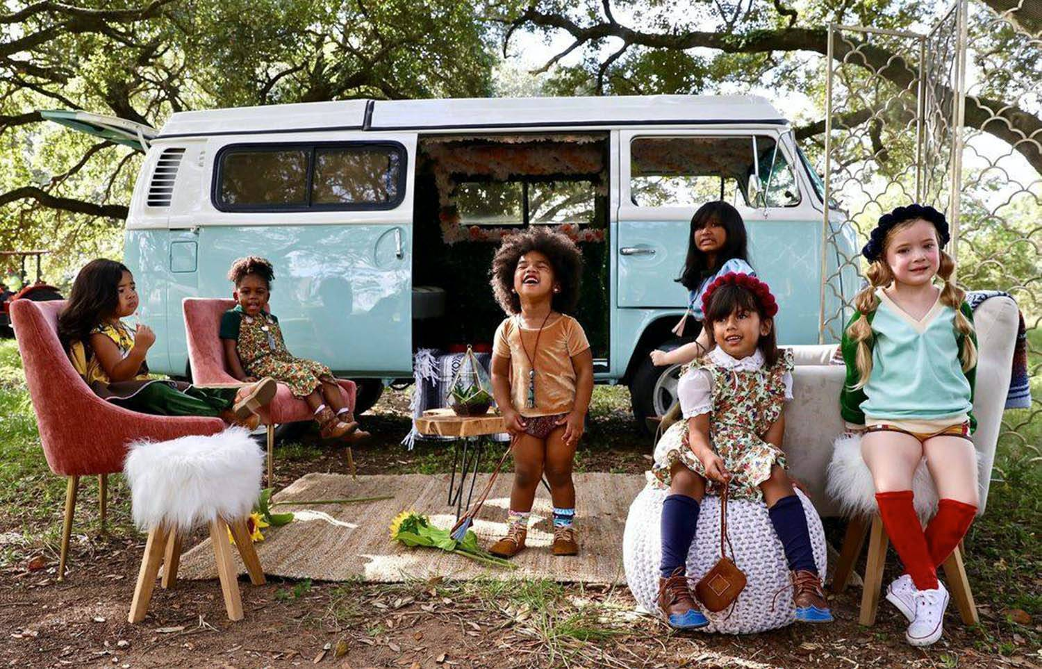 Photo: Iridescent Photography's lifestyle branding photograph of a crew of colorfully dressed kids sitting outside a pale blue VW van.