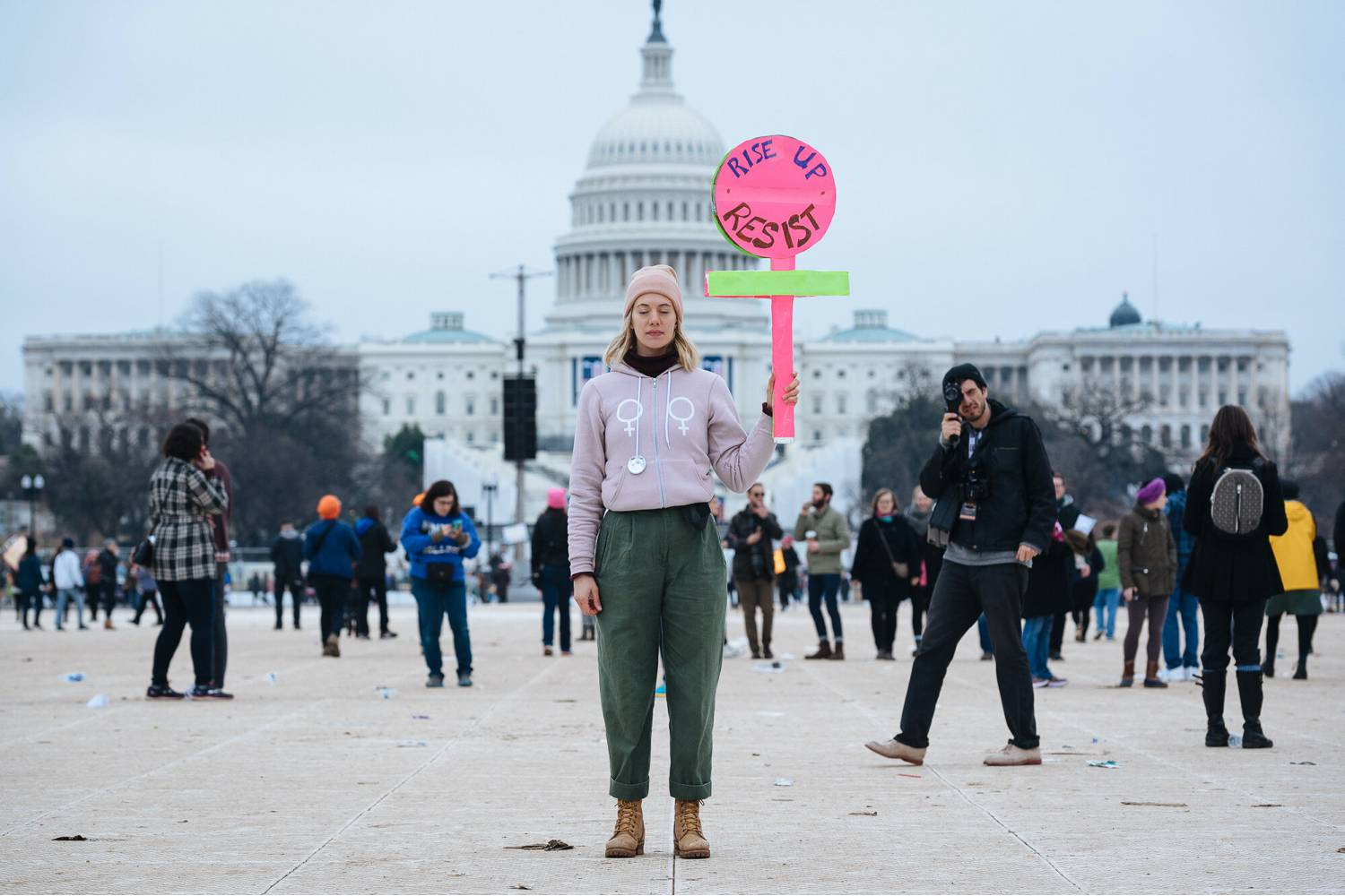 "Photo: Kate Warren's documentary image of a young, white, blonde woman in a pink hat and jacket. She stands in front of the U.S. Capital holding a sign that says, ""Rise up. Resist."""