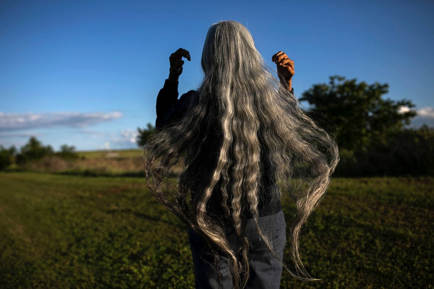 Photo: Maddie McGarvey's portrait of a woman with flowing grey hair shows her brushing her hair back so it flows below her waist as she looks out at a bright blue sky.