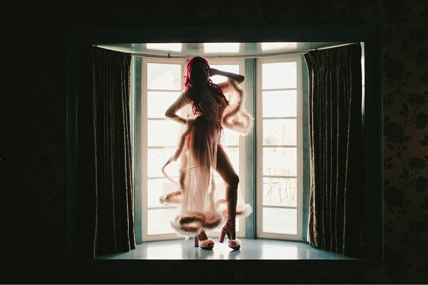 Photo: Michelle Roller's boudoir portrait of a pink-haired woman wearing a silk and fur robe as she stands on a platform before a large bay window.