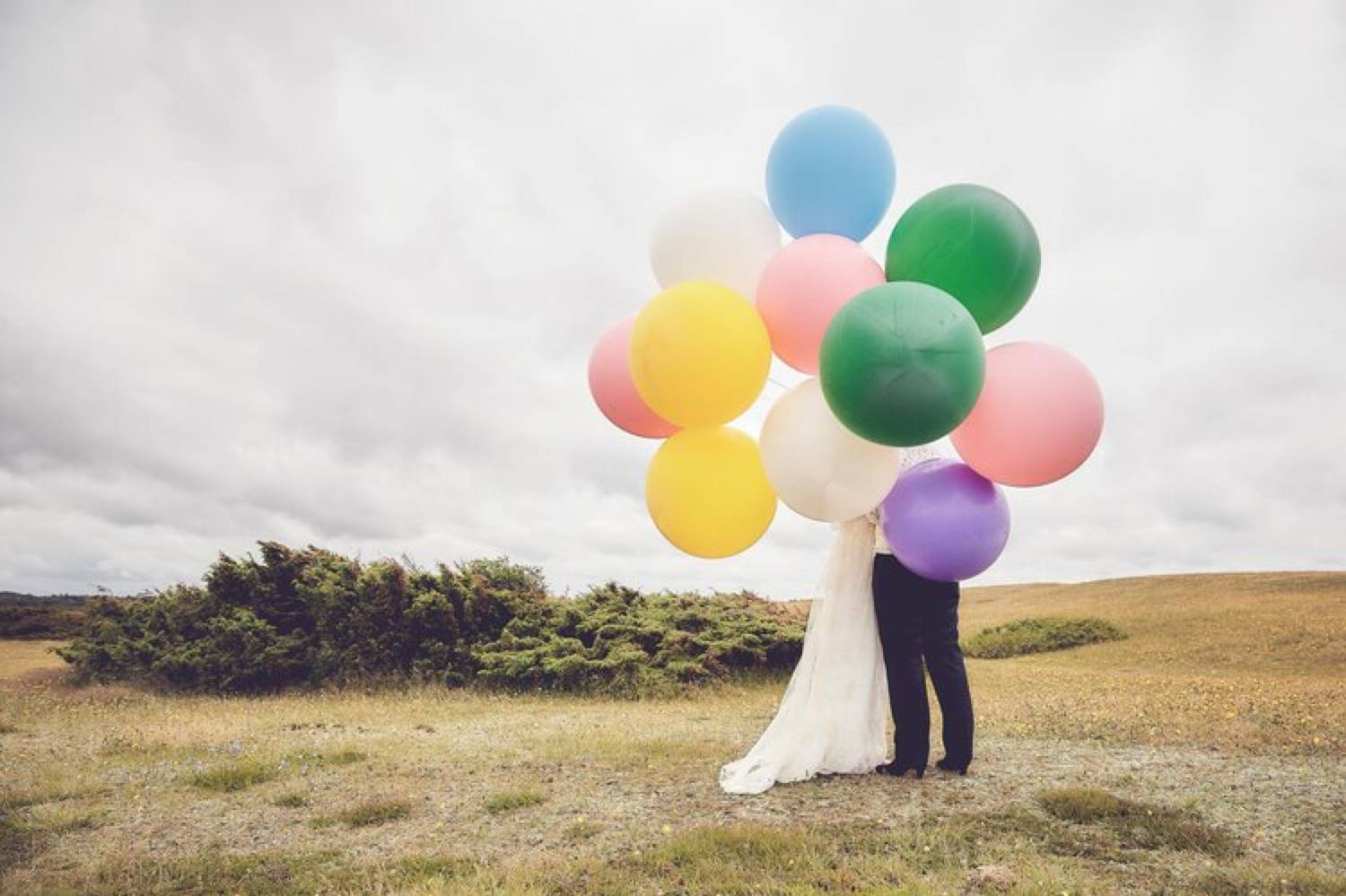 Photo: Mille Stengaard's portrait of a bride and groom is shot against a plane, grey sky. The couple holds a massive bunch of colorful balloons that hides their faces.