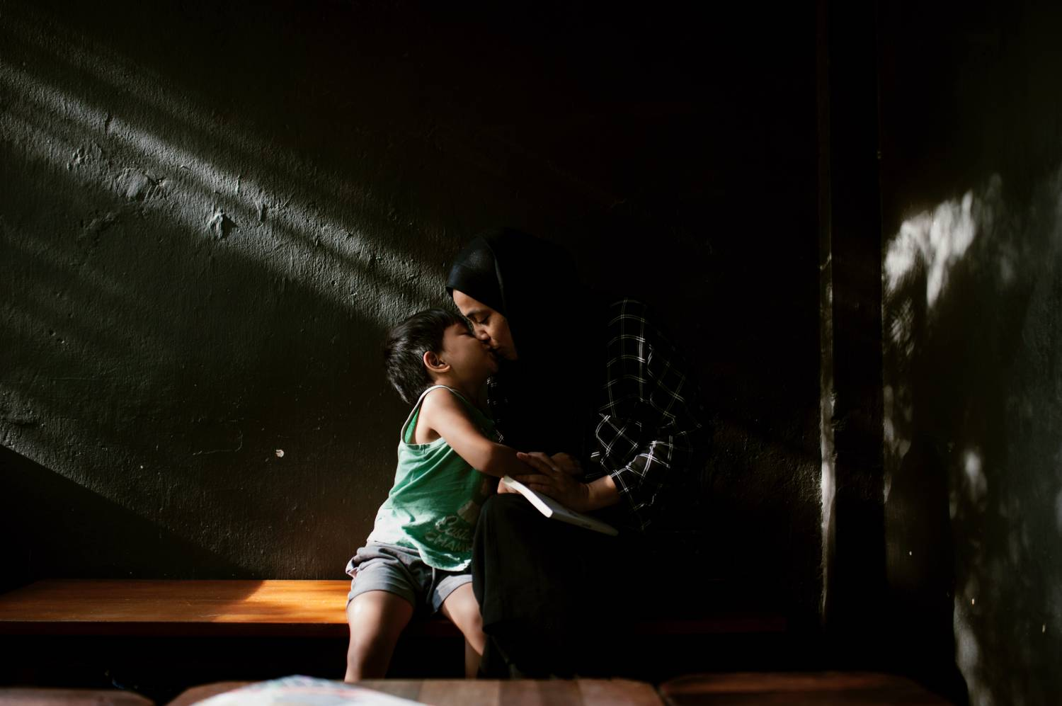 Photo: Min Mohd's moody portrait shows a little boy kissing his mother as they lean into a beam of light.