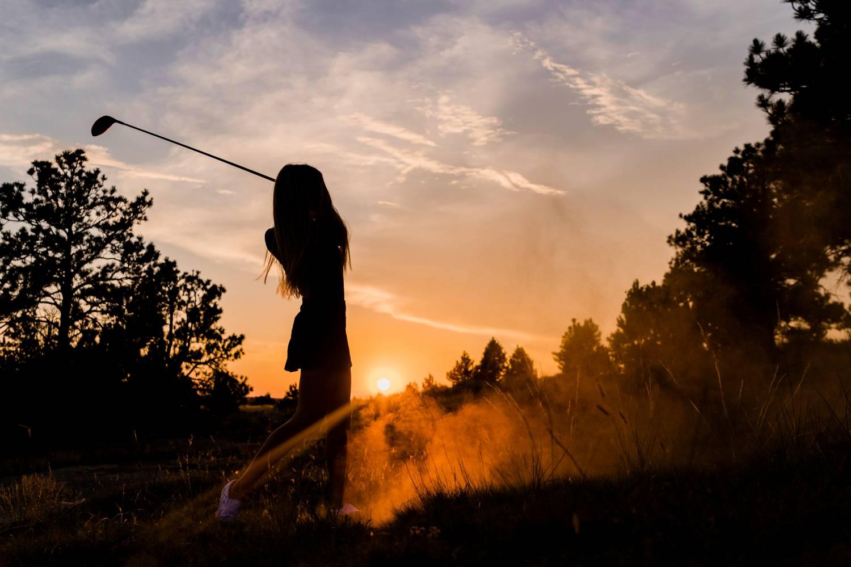 A senior girl swings at golf club at sunset.