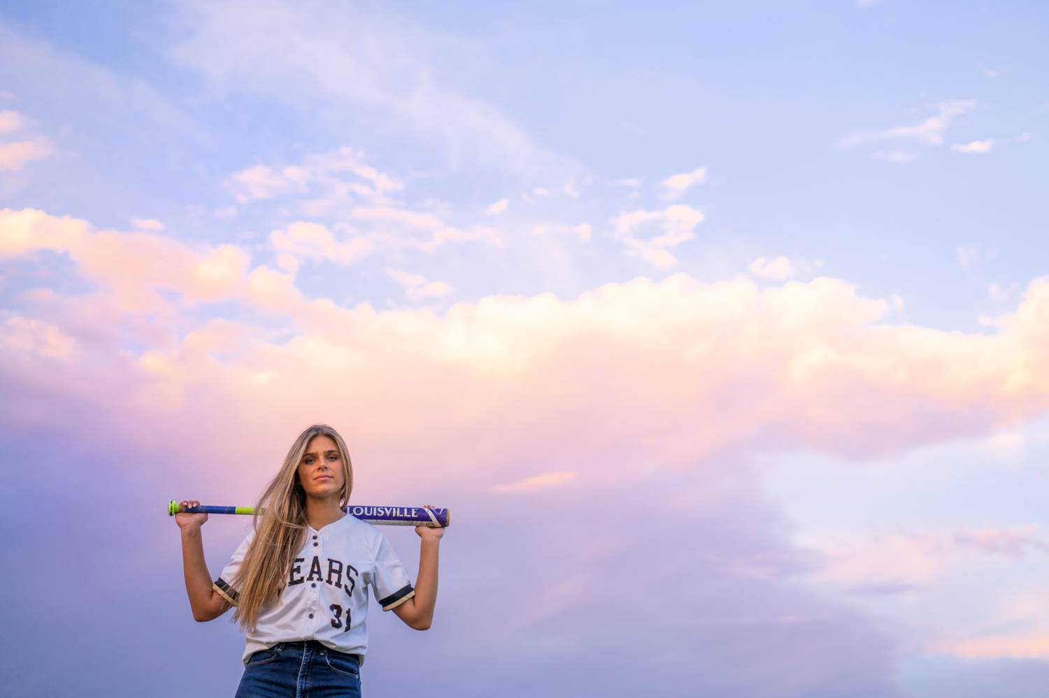 A senior girl holds a baseball bat over her shoulders. Behind her are clouds and a purpose sky at sunset.