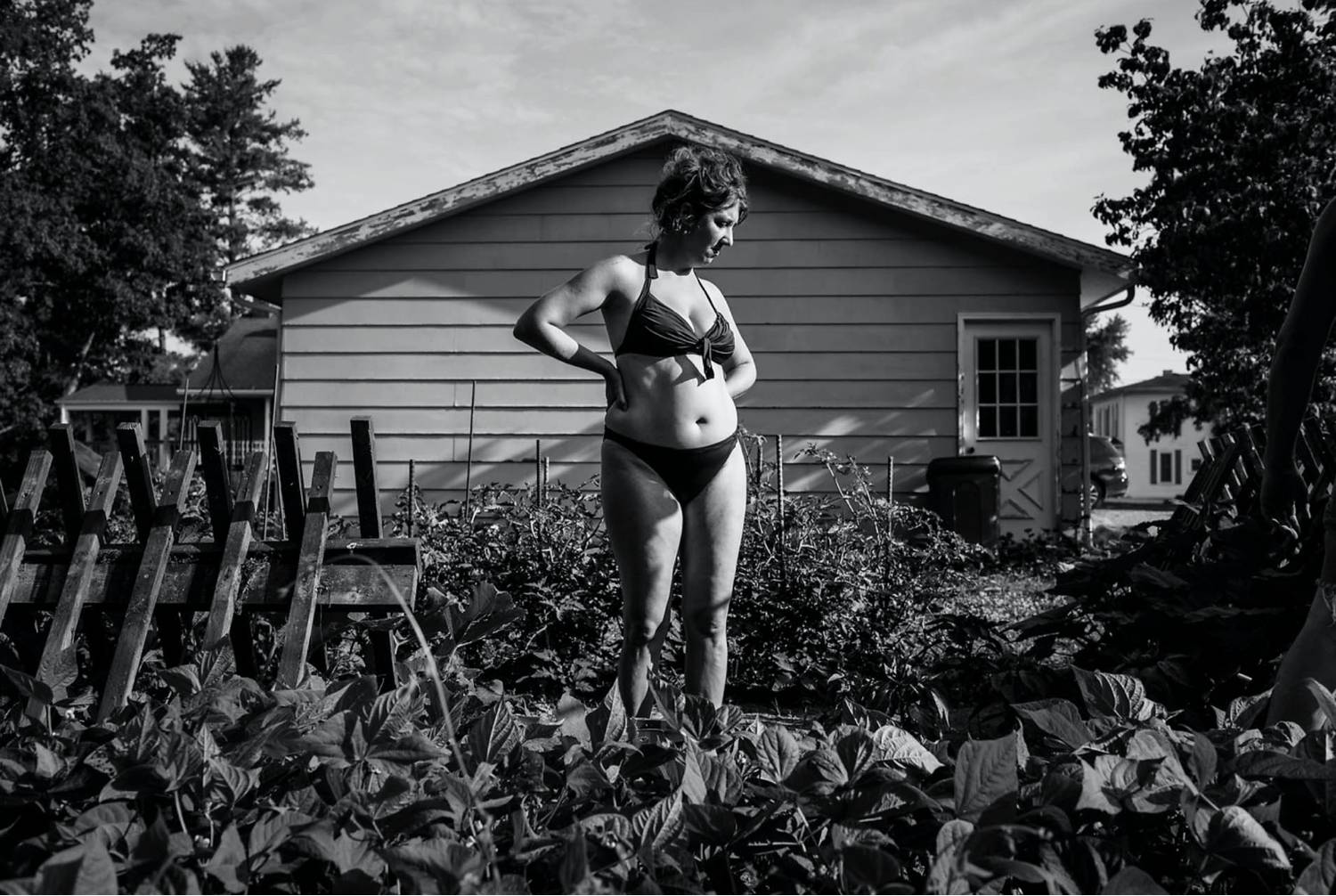 Photo: Rebecca Kiger's black and white photo of a woman in a bikini standing in her brightly sunlit garden.