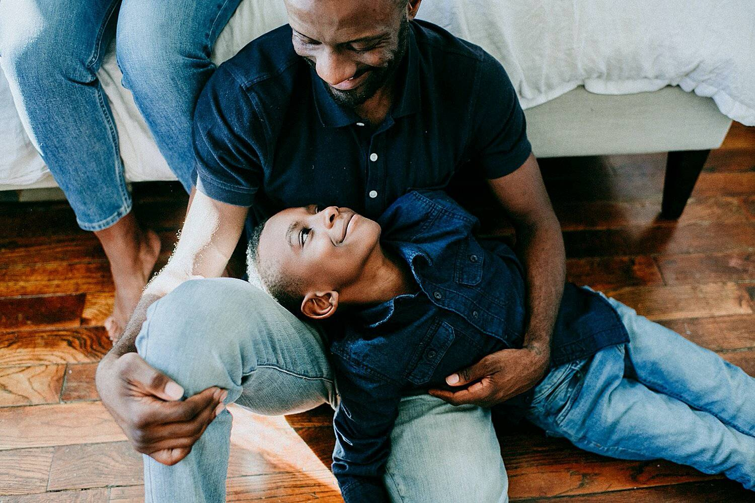 Photo: Yasmina Cowan's in-home lifestyle portrait of a dad sitting on a hardwood floor and leaning against a bed as his son reclines in his lap smiling into his face.