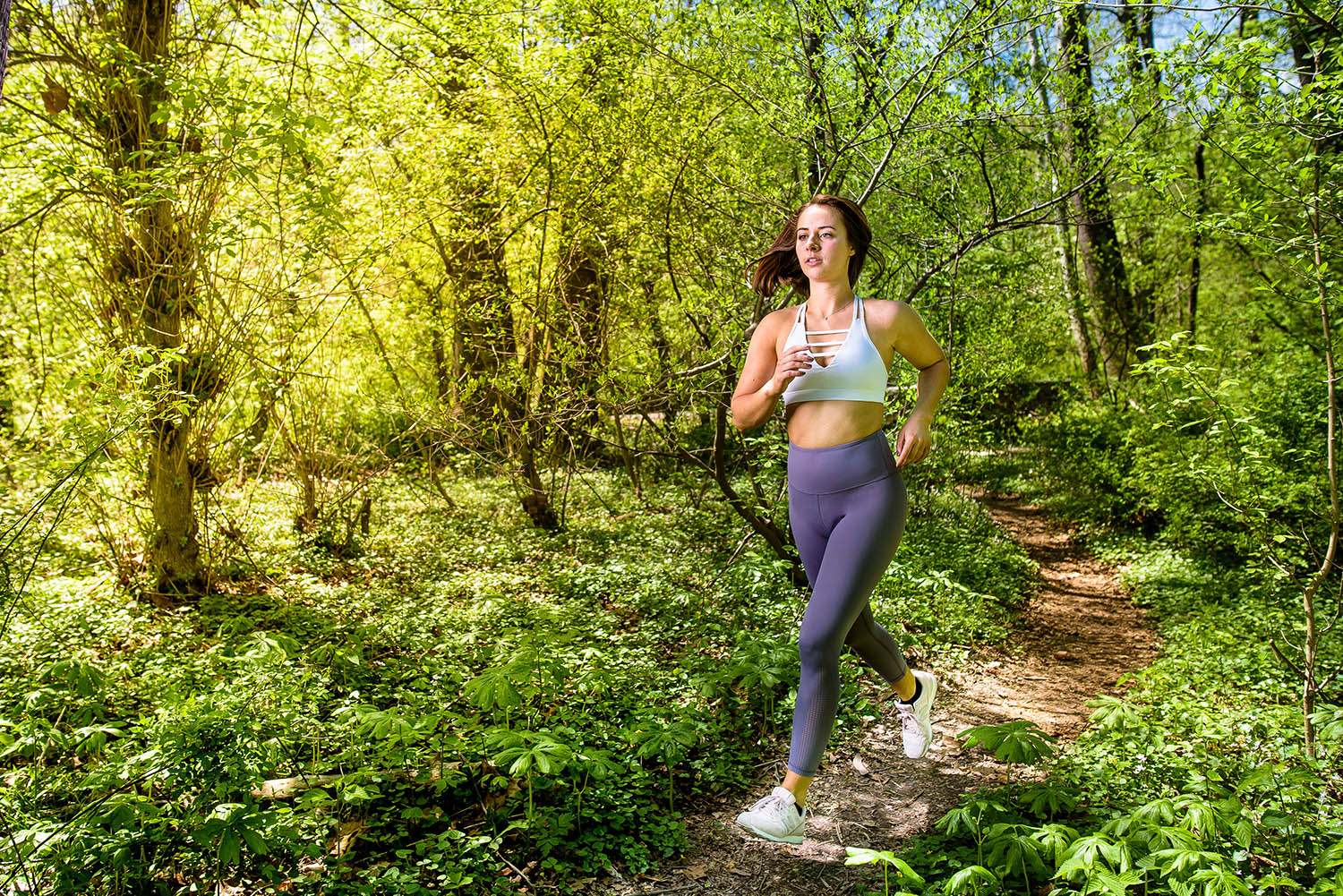 A runner jogs through the woods in this commercial photo by Joe Dantone