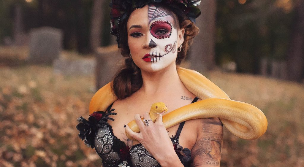 Mariah Gale Creative photographs a Mexican woman whose face is half-painted with a sugar skull. She wears a crown of black roses and holds a yellow snake wrapped around her shoulders.