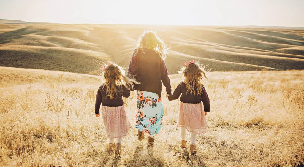 Three sisters dressed in denim jackets and long skirts walk hand-in-hand towards a sunset