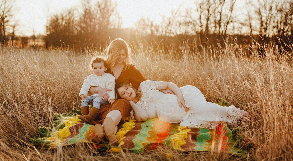 family on blanket in field