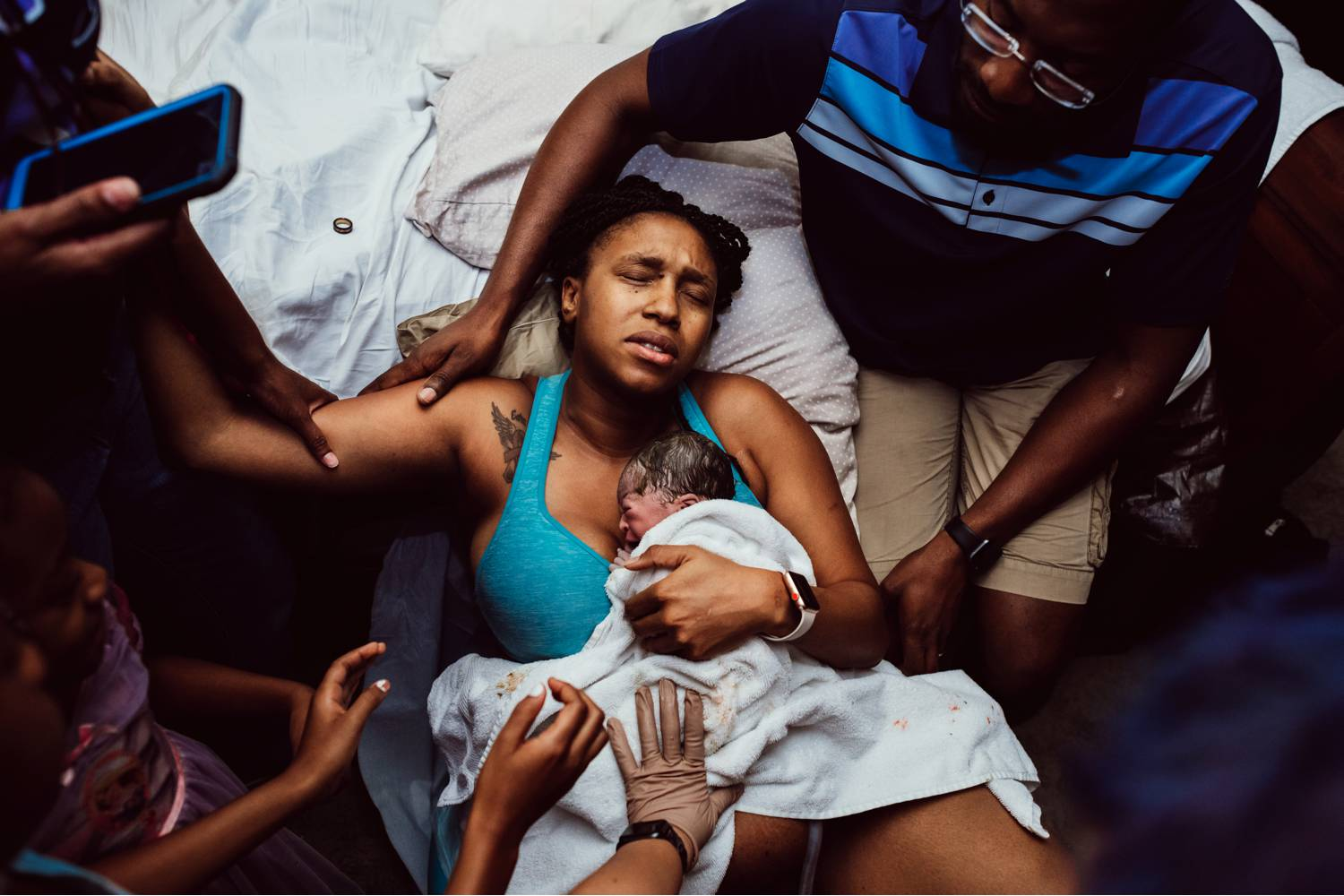 A mother embraces her newborn against her chest after just giving birth. She is surrounded by the supportive arms of her friends and family.