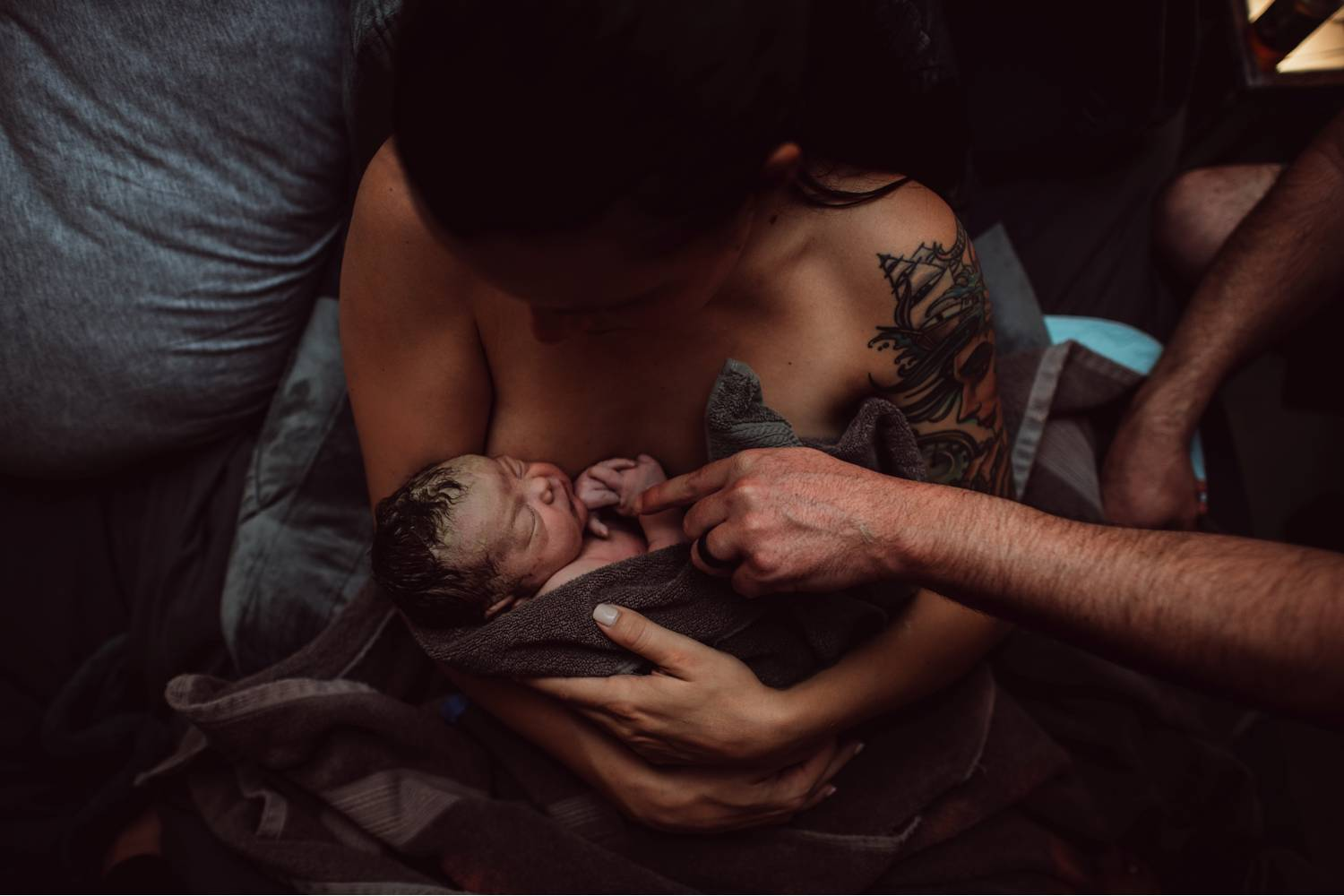 New parents cradle their infant moments after delivering the baby in a home birth