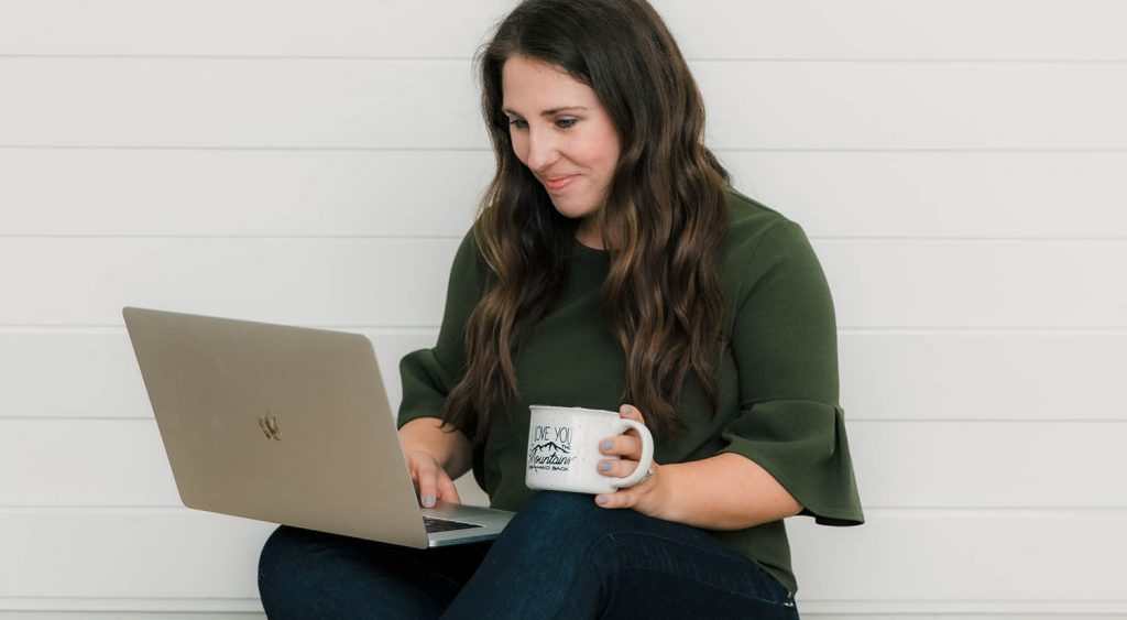 Photographer Logan Fahey works on her laptop with a mug of coffee in her hand