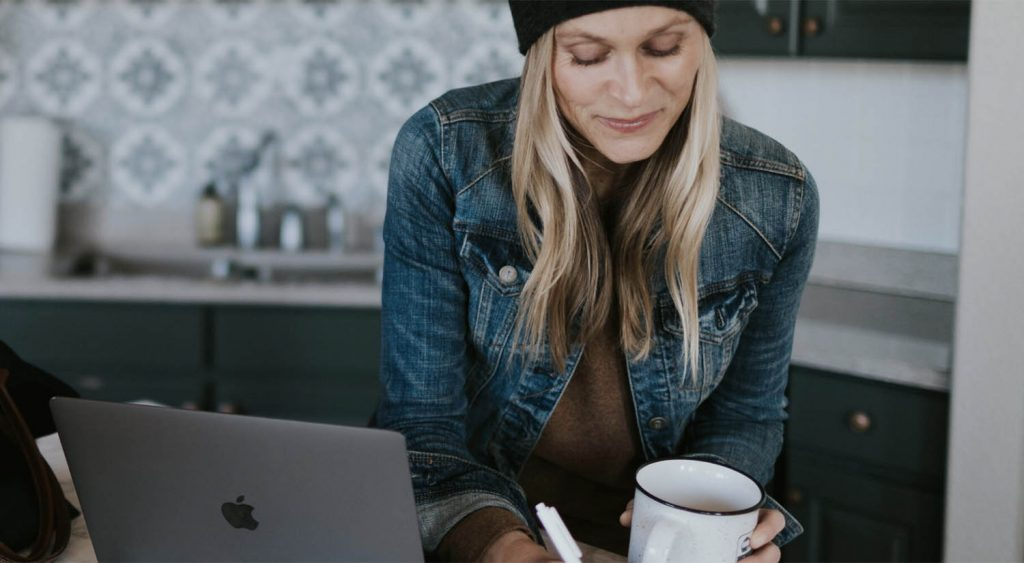 Lifestyle photograph of photographer Jenni Maroney working at her laptop with a cup of coffee in her hand. She wears a denim jacket and a black ski cap.