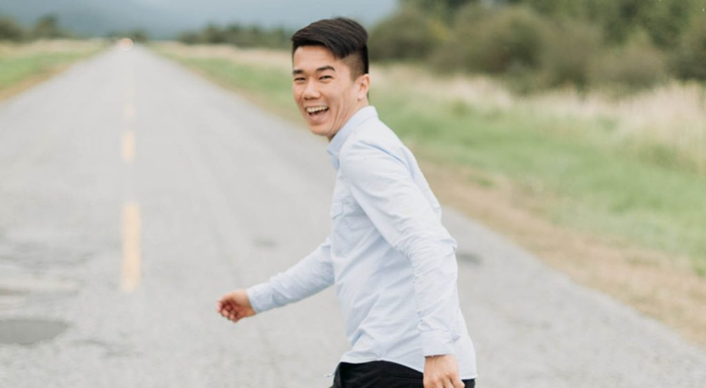 Photographer Wilson Lau looks back over his shoulder laughing as he jogs down a country road