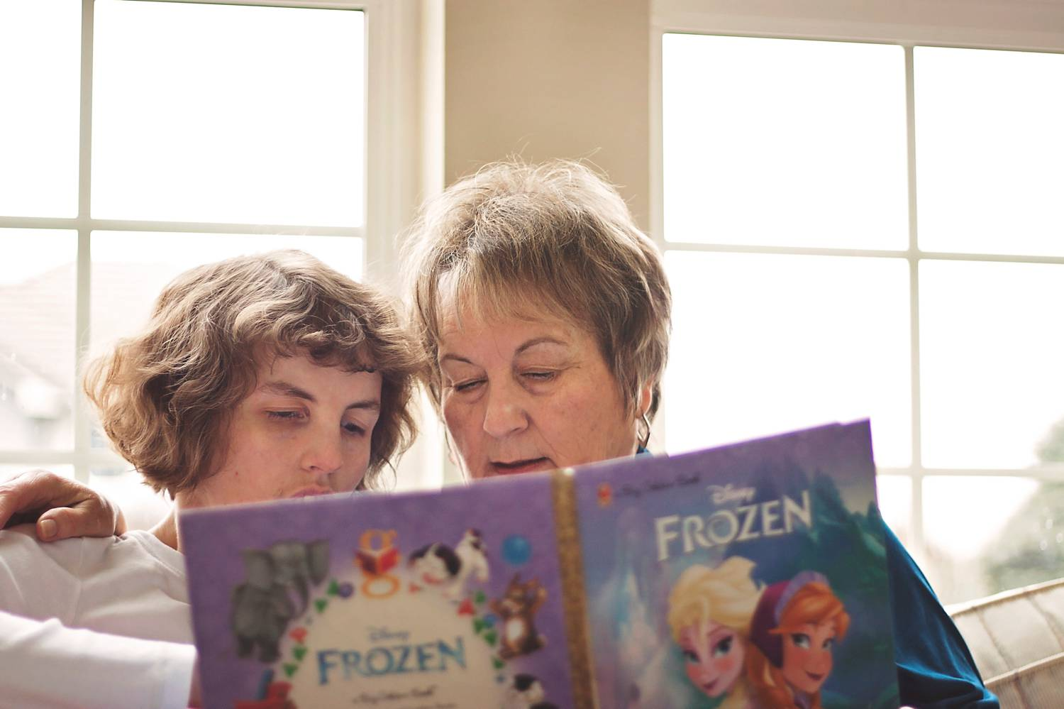A mom sits on the sofa at home with her special needs daughter reading a book.