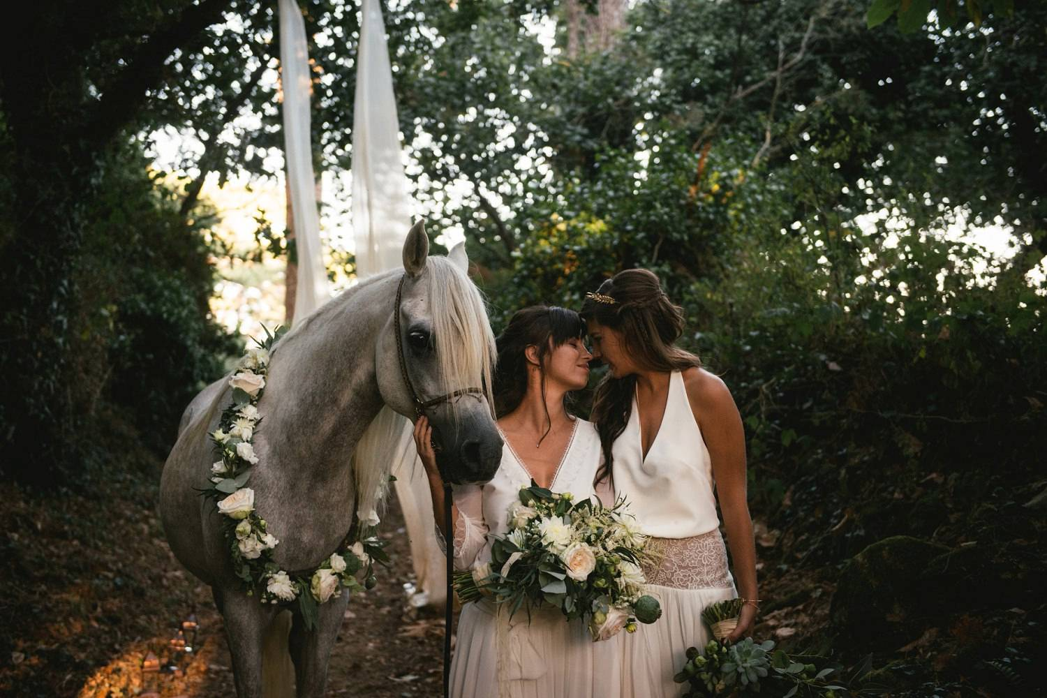 Two brides pose in a forest with an Arabian horse wearing a wreath of flowers