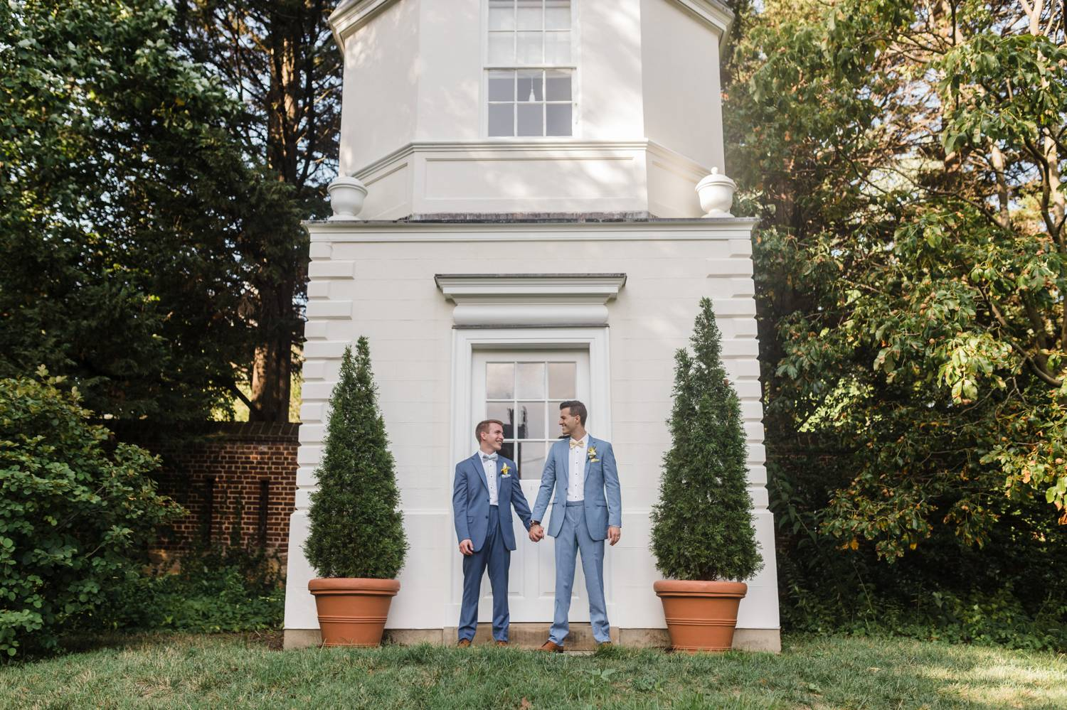 Two grooms dressed in gray suits hold hands in front of a tall white chapel
