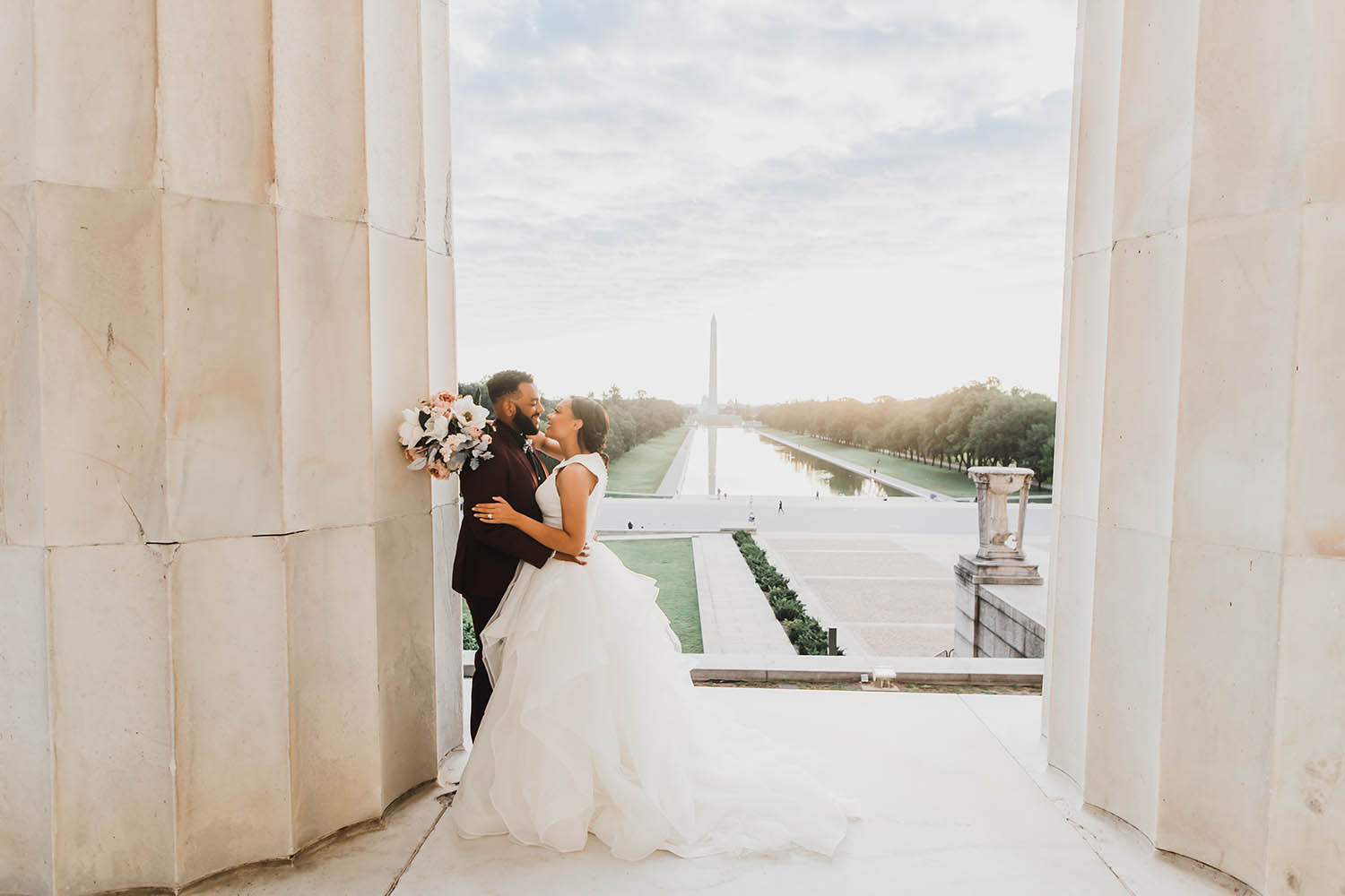 A bride and groom embrace while leaning against a massive column in the Lincoln Memorial. In the background the Washington Monument soars over the reflection pool.