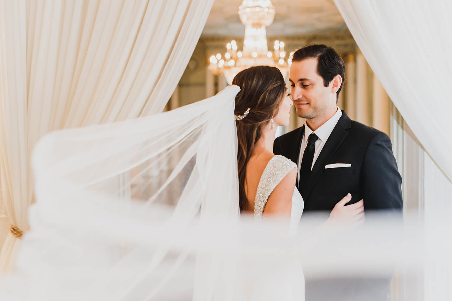 A bride and groom dance their first dance in an elegant ballroom as her veil floats out behind her.