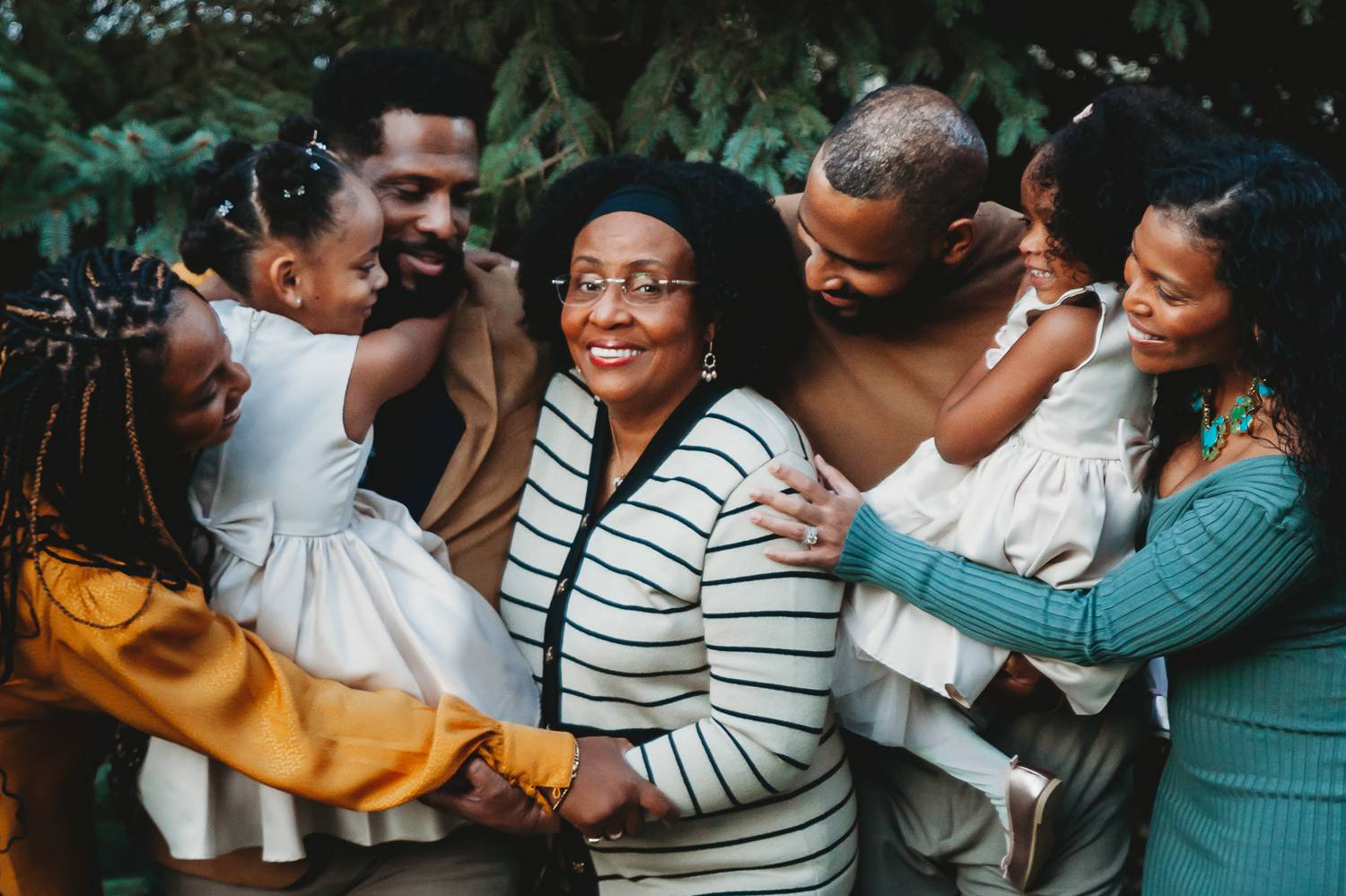 A smiling Black family gathers around the matriarch and hugs one another close