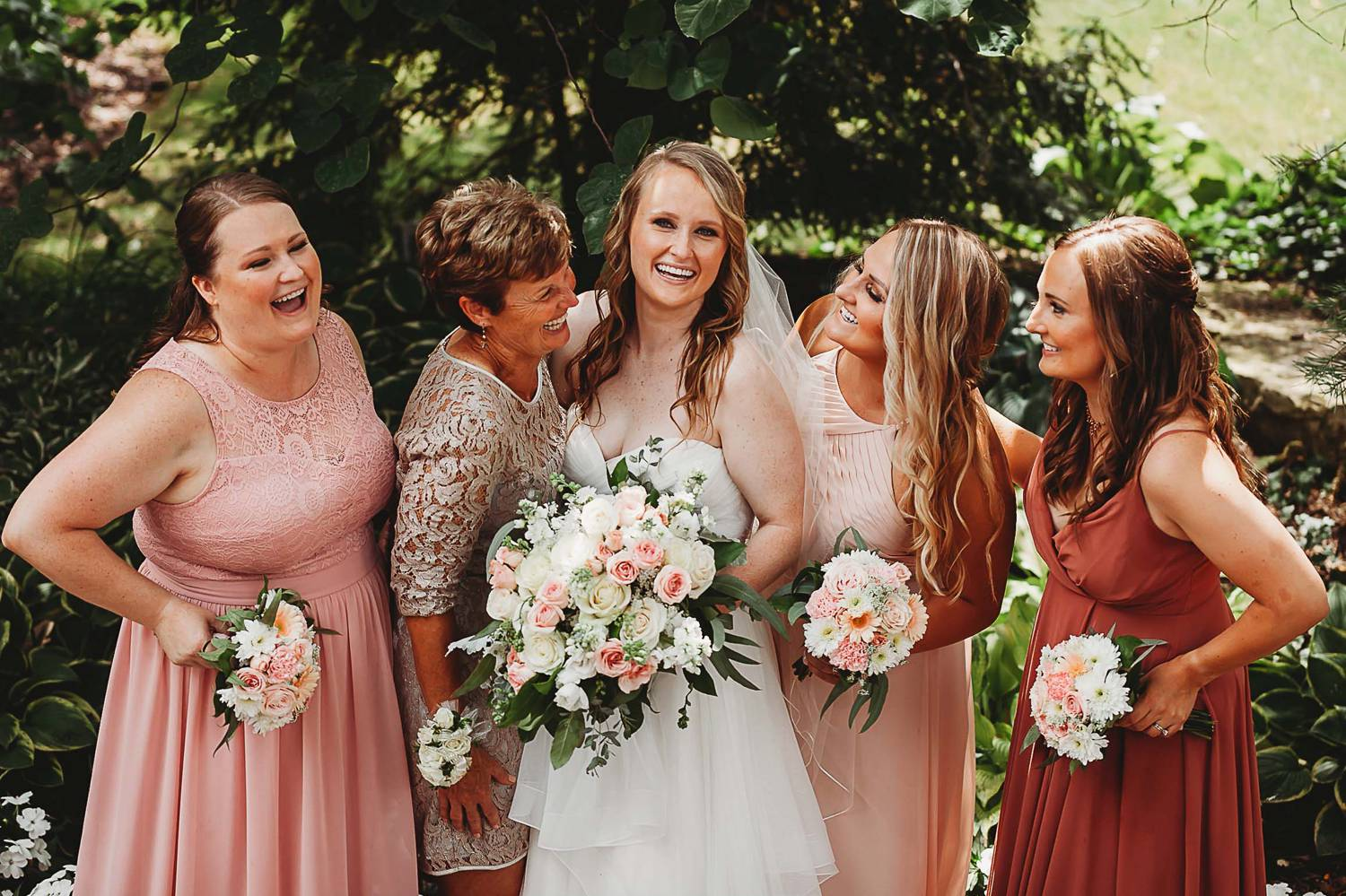 Bridesmaids in pink dresses surround a smiling bride