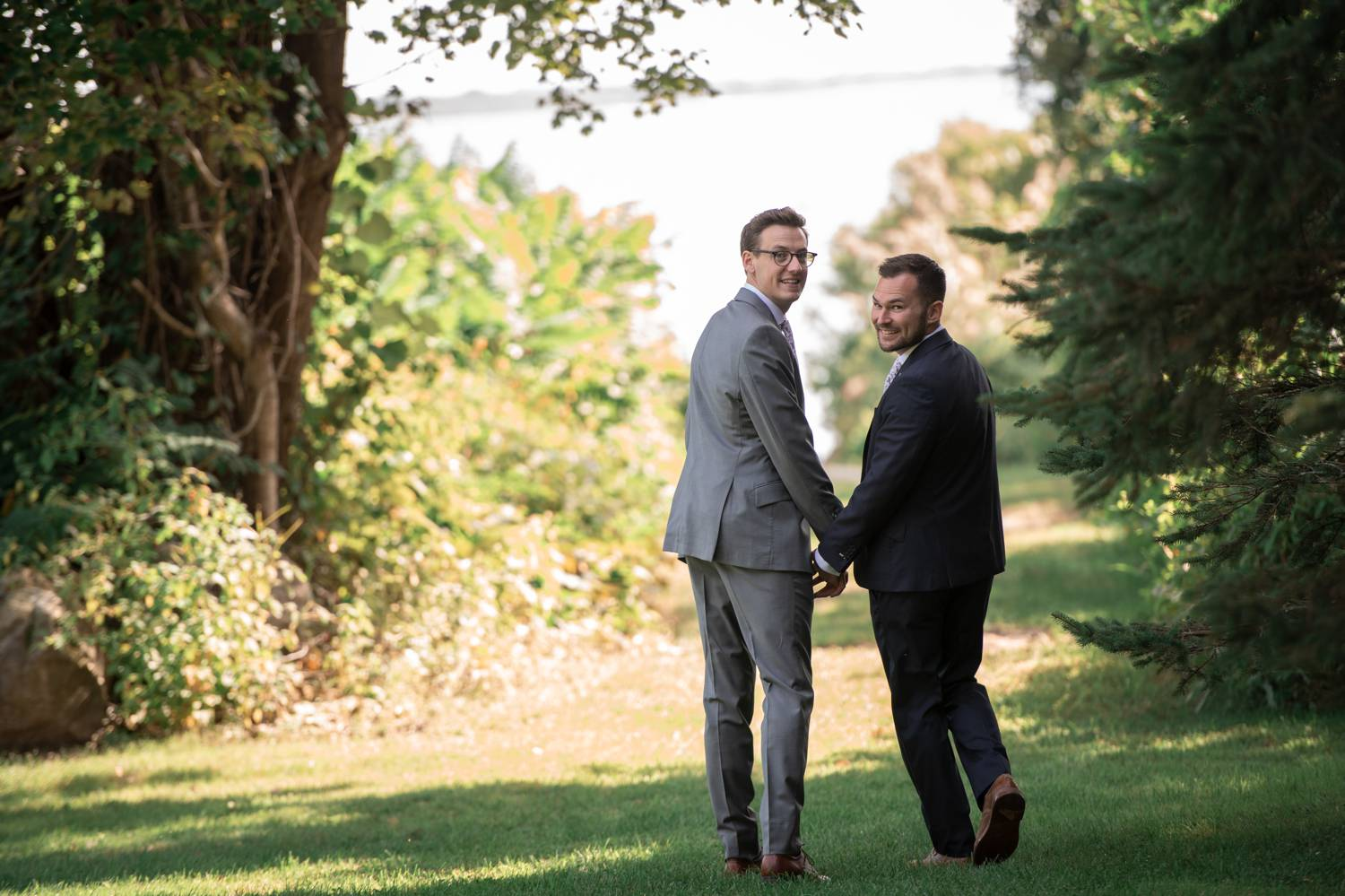Two grooms stroll across a broad lawn, smiling as they look back over their shoulders