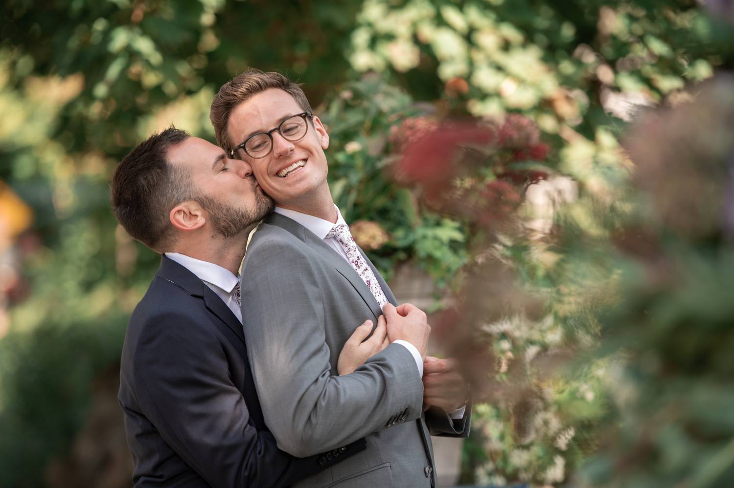 A groom in a charcoal suit stands behind his husband and kisses his cheek for an outdoor wedding day portrait