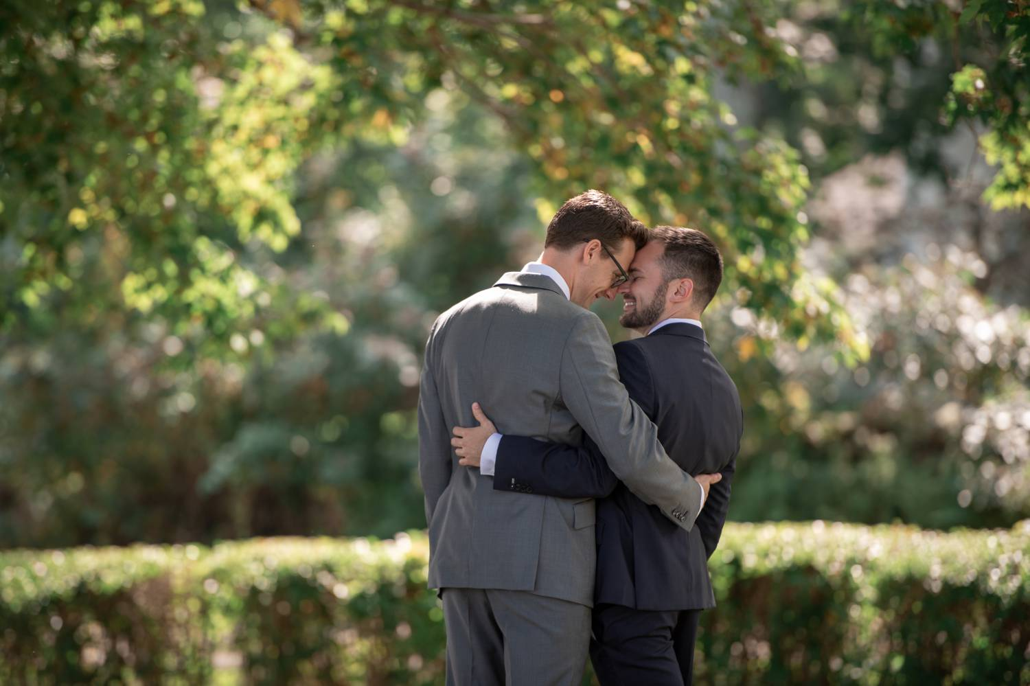 Two men stand forehead to forehead with their arms wrapped around each other