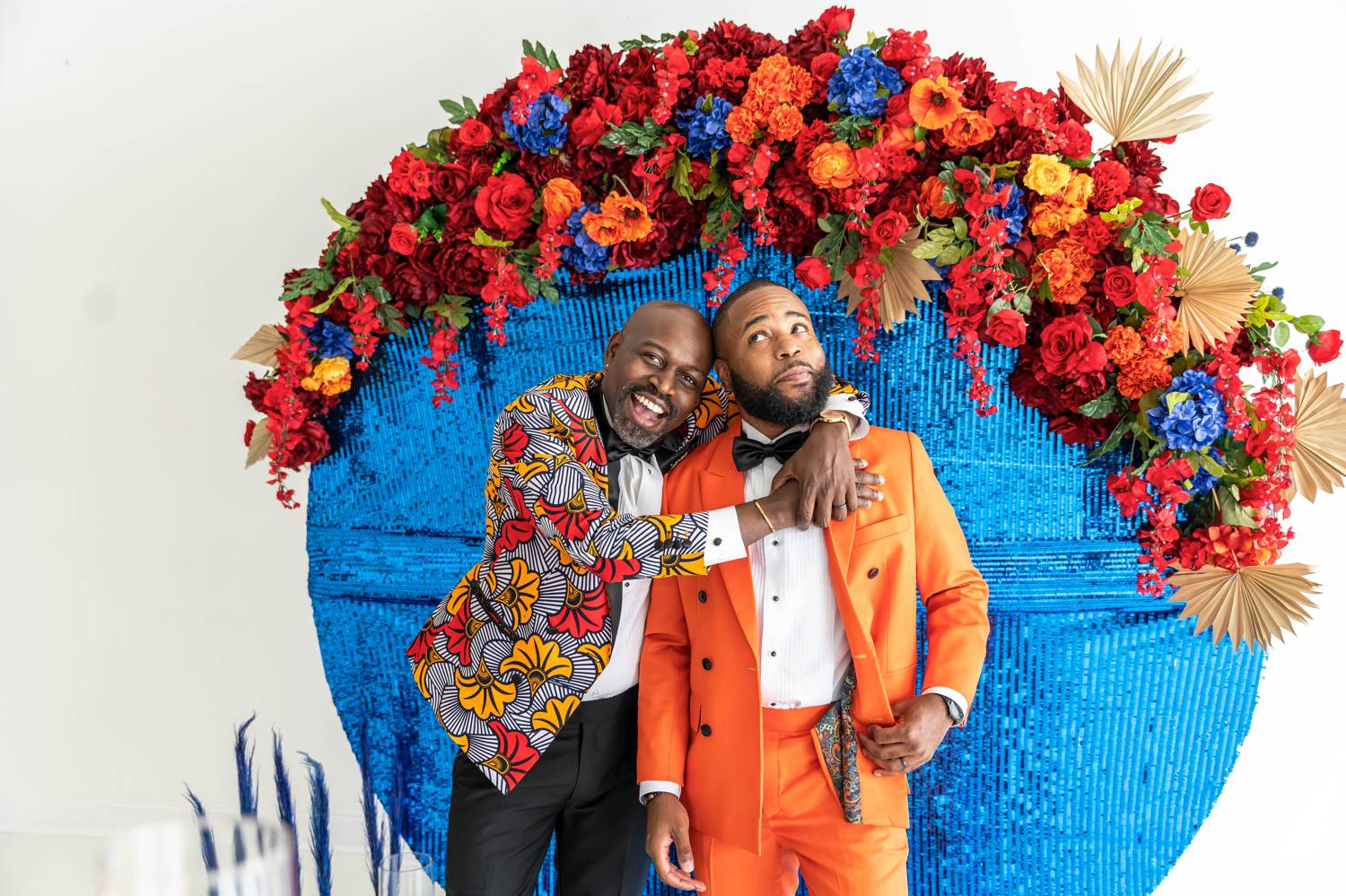 A groom in a colorful jacket wraps his arms around the shoulders of his husband who wears a bold orange suit