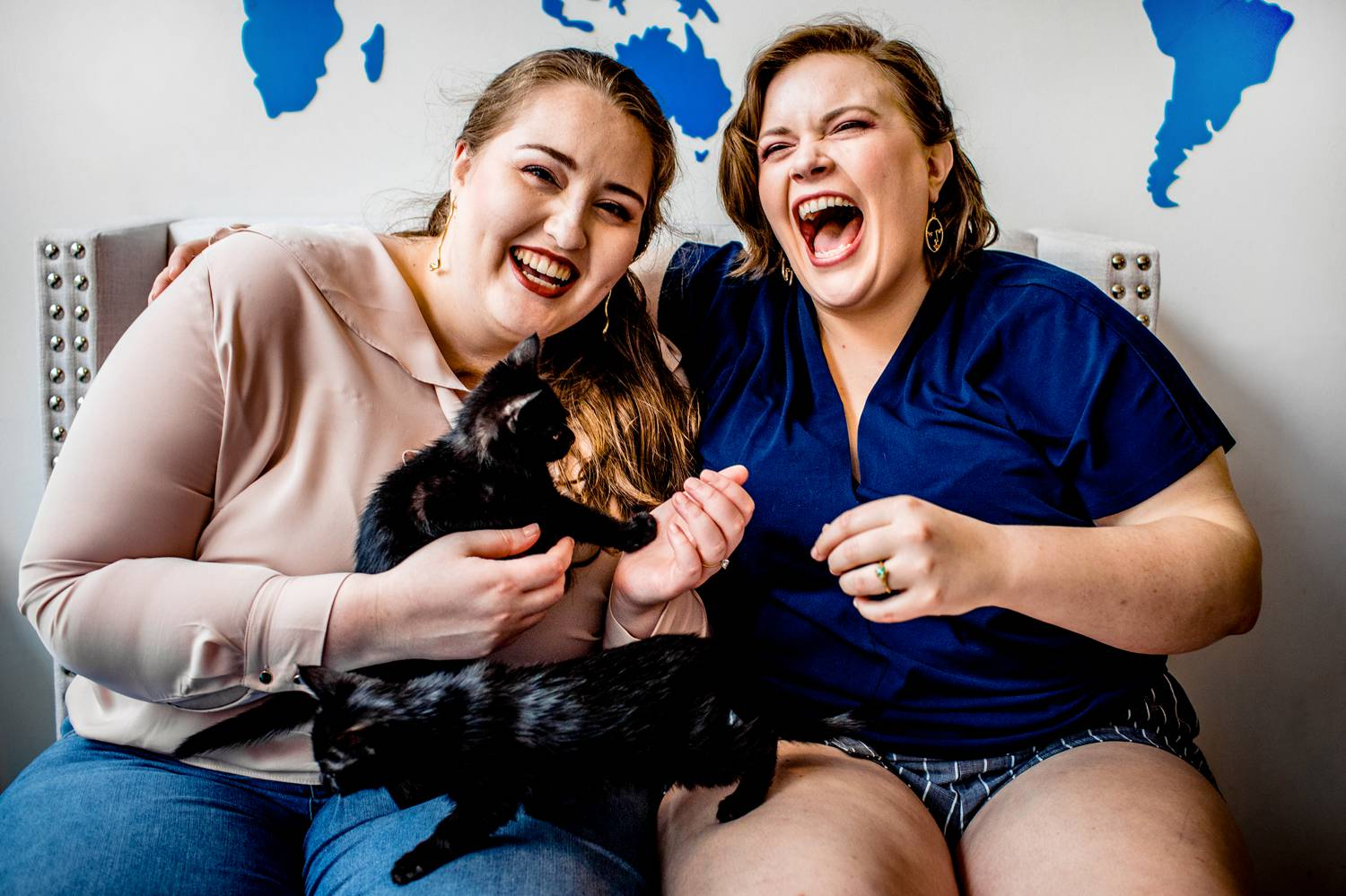 Two engaged women sit in a cat cafe and laugh as tiny kittens swarm them