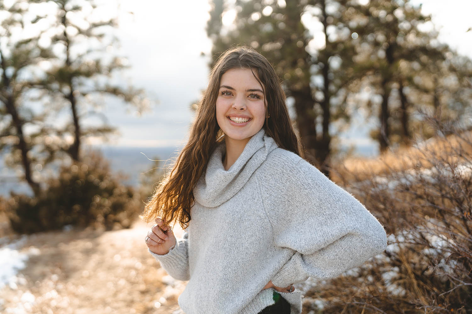 A high school senior girls poses wearing a gray sweater on a Montana hilltop