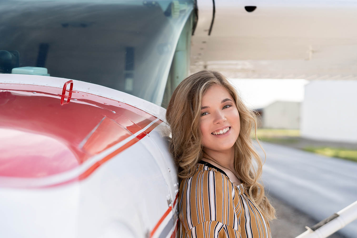A high school senior girl leans agains the side of a small airplane
