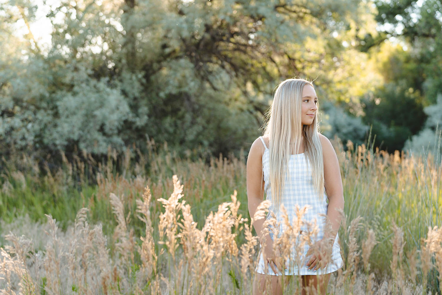 A high school senior girl in a white mini dress stands in a field looking into the distance