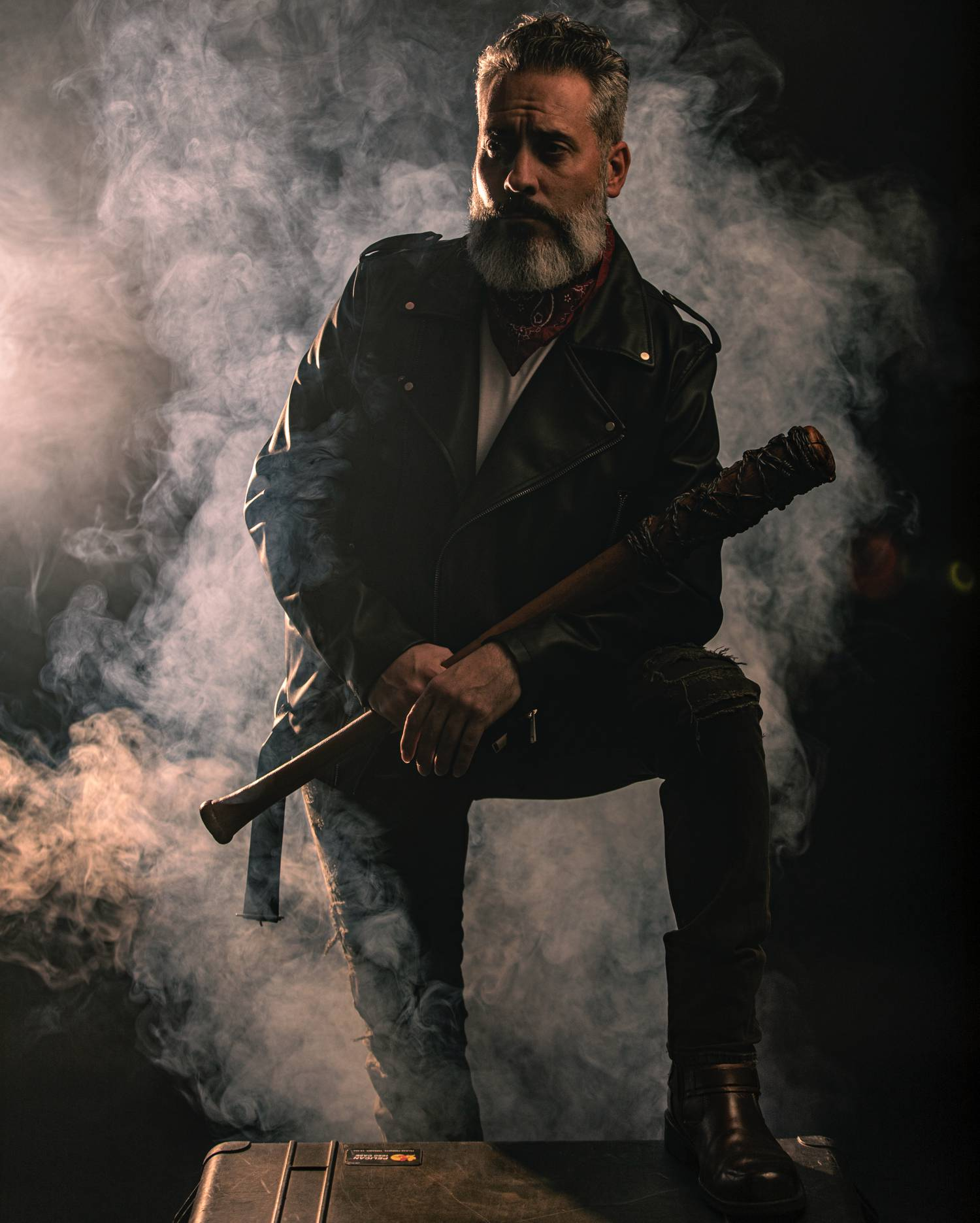 In this styled tribute photograph by Alexander Worth of Jawfox Photography, a man cosplays Negan from The Walking Dead, wearing a leather jacket and carrying the villain's barbed wire-wrapped bat, Lucille. Behind the model the air is full of dark smoke.